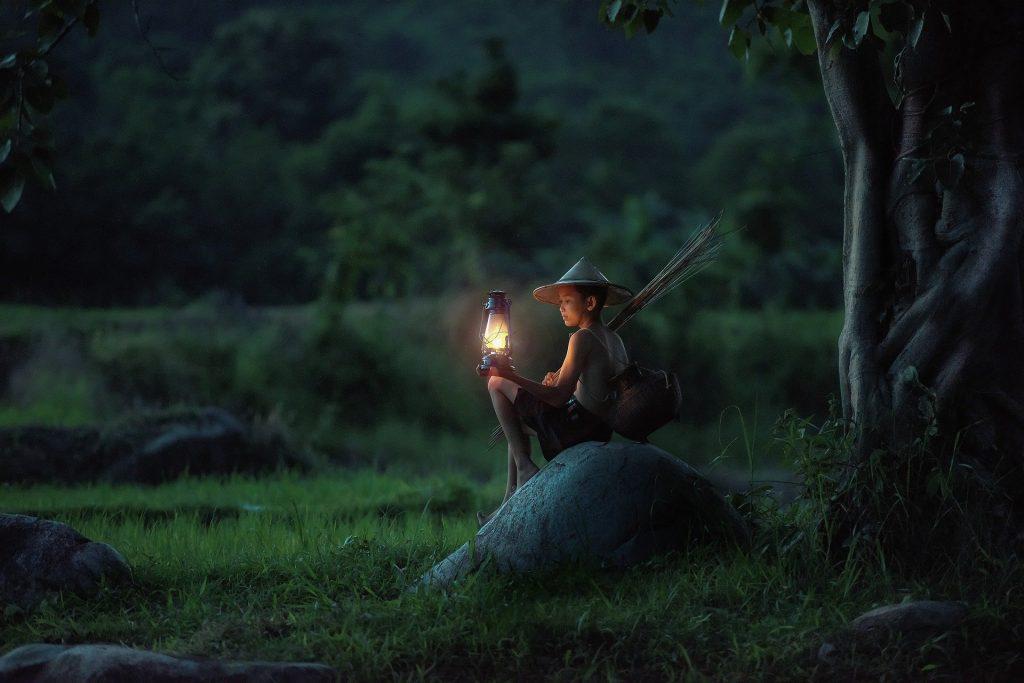 Une jeune garçon dans la forêt avec une lanterne