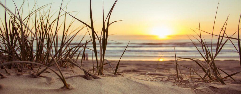 un soleil couchant depuis une dune avec la mer